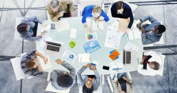 Image of ten people around a desk having a business meeting.