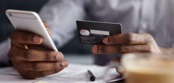 Image of hands holding a mobile phone and credit card