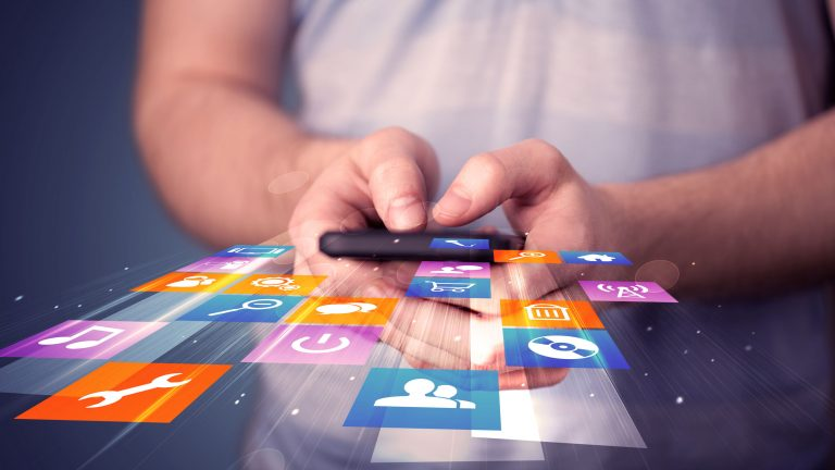 Image of Man holding smart phone with colourful application icons coming out