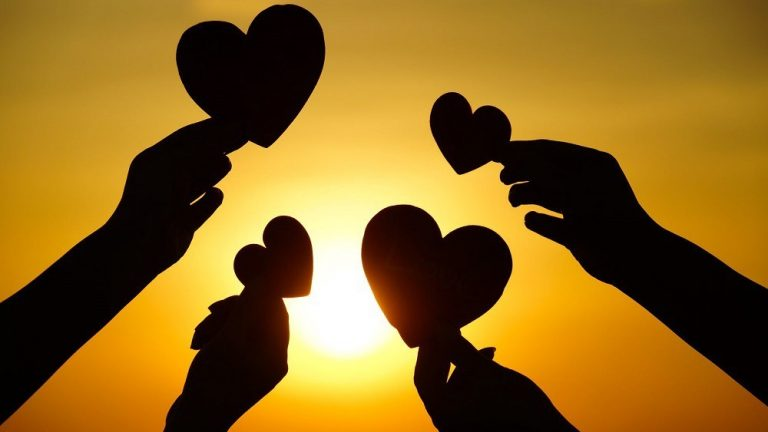Image of hands with love heart shapes in the fingers