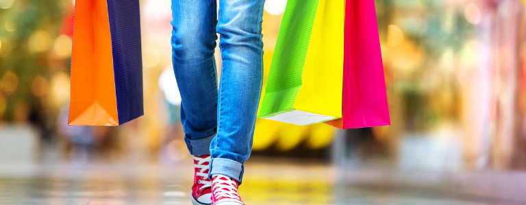 Image of somebodies legs wearing blue jeans and red sneakers carrying multi coloured shopping bags.