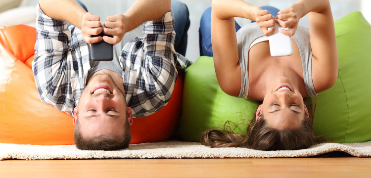 Image of Man and woman lying on bean bags looking at mobile phones.