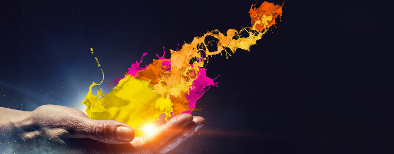 Hand holding a orb of light and a splash of yellow, pink and orange paint