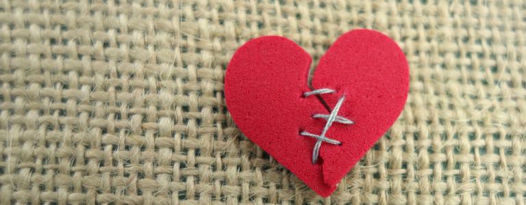felt heart, stitched back together. On a hessian background