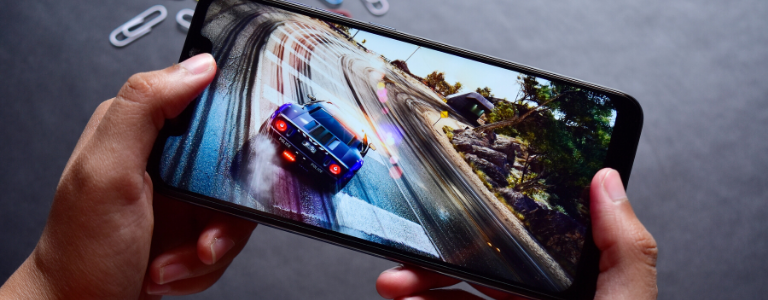 hands holding a mobile phone with a car racing on a track on screen