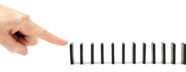 Hand with outstretched finger ready about to touch a line of dominoes