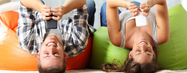 Image of man and woman lying on bean bags looking at their mobile phones